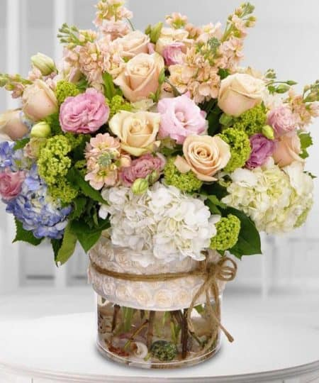 Premium floral varieties of roses, hydrangea, greens and more are filled in a glass vase bearing a designer ribbon (Ribbon designs will vary)
